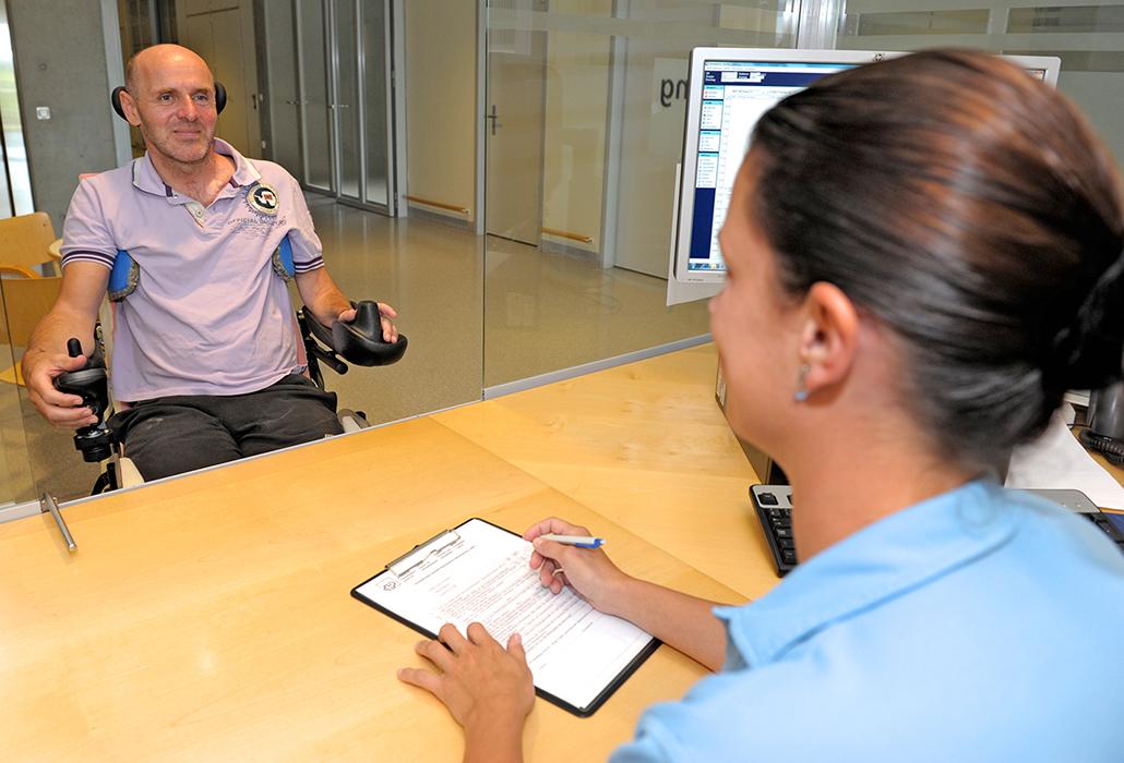 Patient wird an der Anmeldung Radiologie bedient im Schweizer Paraplegikerzentrum