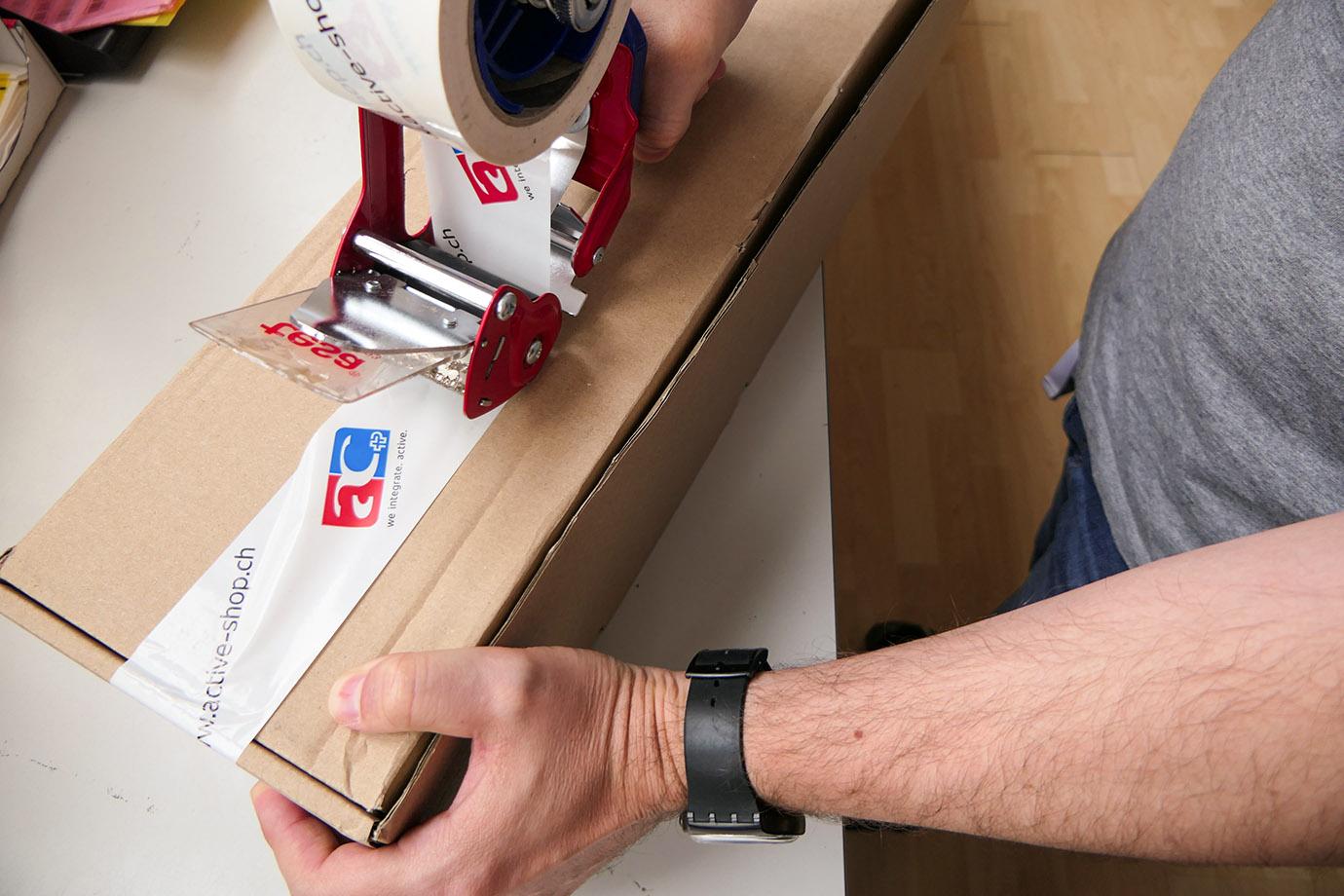 Leonard beklebt ein Paket mit dem Klebeband, worauf das Logo der Active Communication abgebildet ist