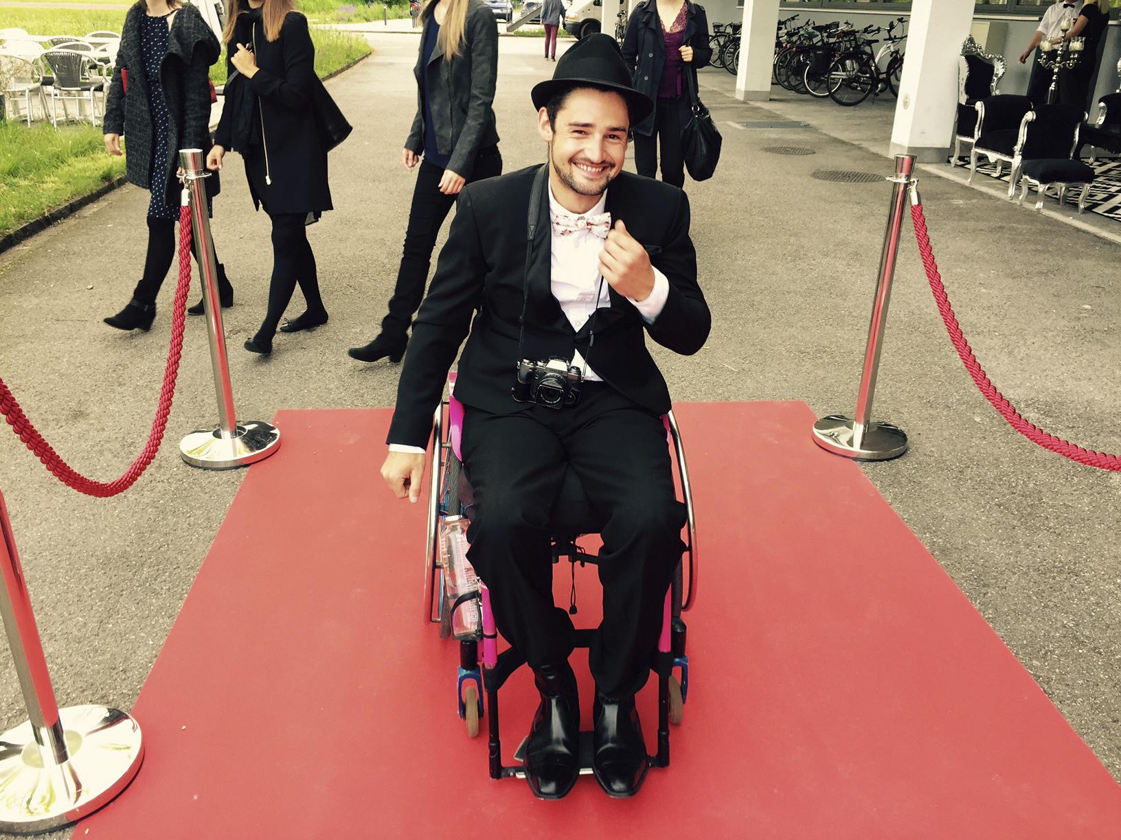Der Rollstuhlfahrer besucht eine Veranstaltung mit rotem Teppich.