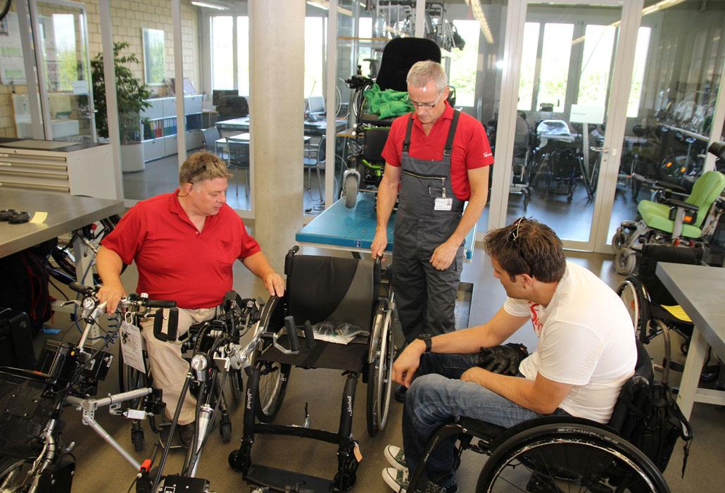 Ein Rollstuhlfahrer lässt sich von einem Rollstuhlfahrer beim Kauf eines Rollstuhls beraten.