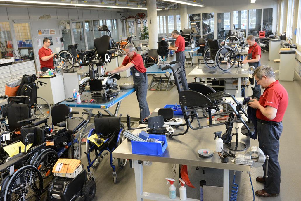 Rollstuhlmechaniker arbeiten in der Werkstatt an Rollstühlen.